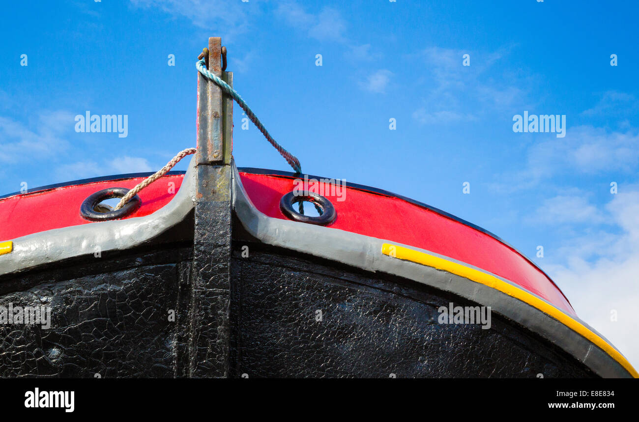 Red black and yellow painted prow of a barge in a Bristol boatyard - Stock Image