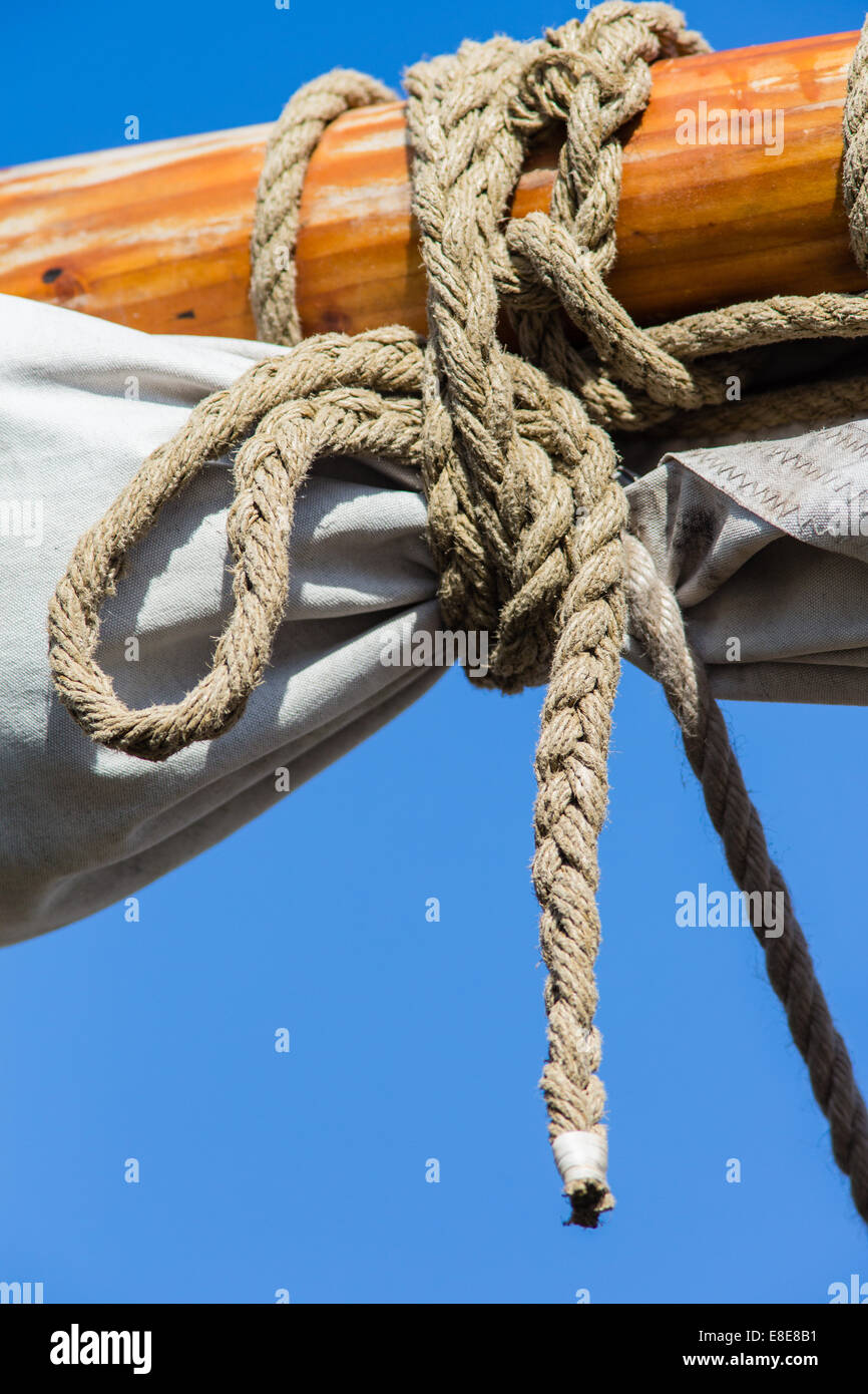 Knotted rope used tie up a sail on a sailing yacht - Stock Image
