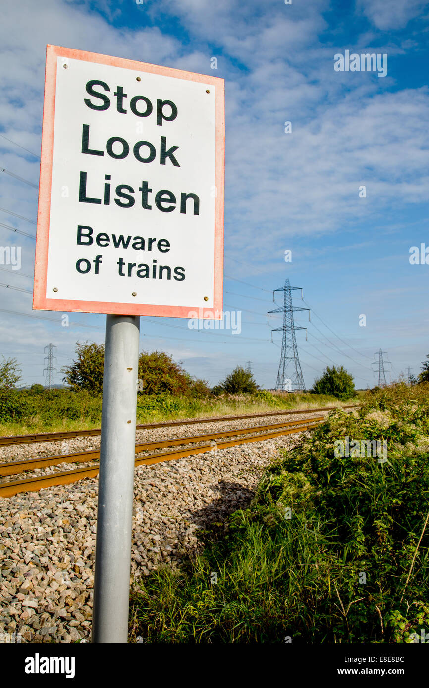 Foot crossing of a busy railway line with a warning sign to stop look and listen for trains - Stock Image