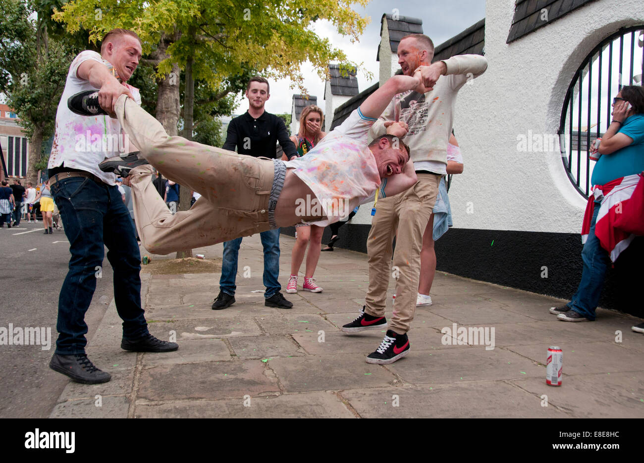 Two men swinging a third in street at Annual Notting Hill Carnival in London 2014 - Stock Image