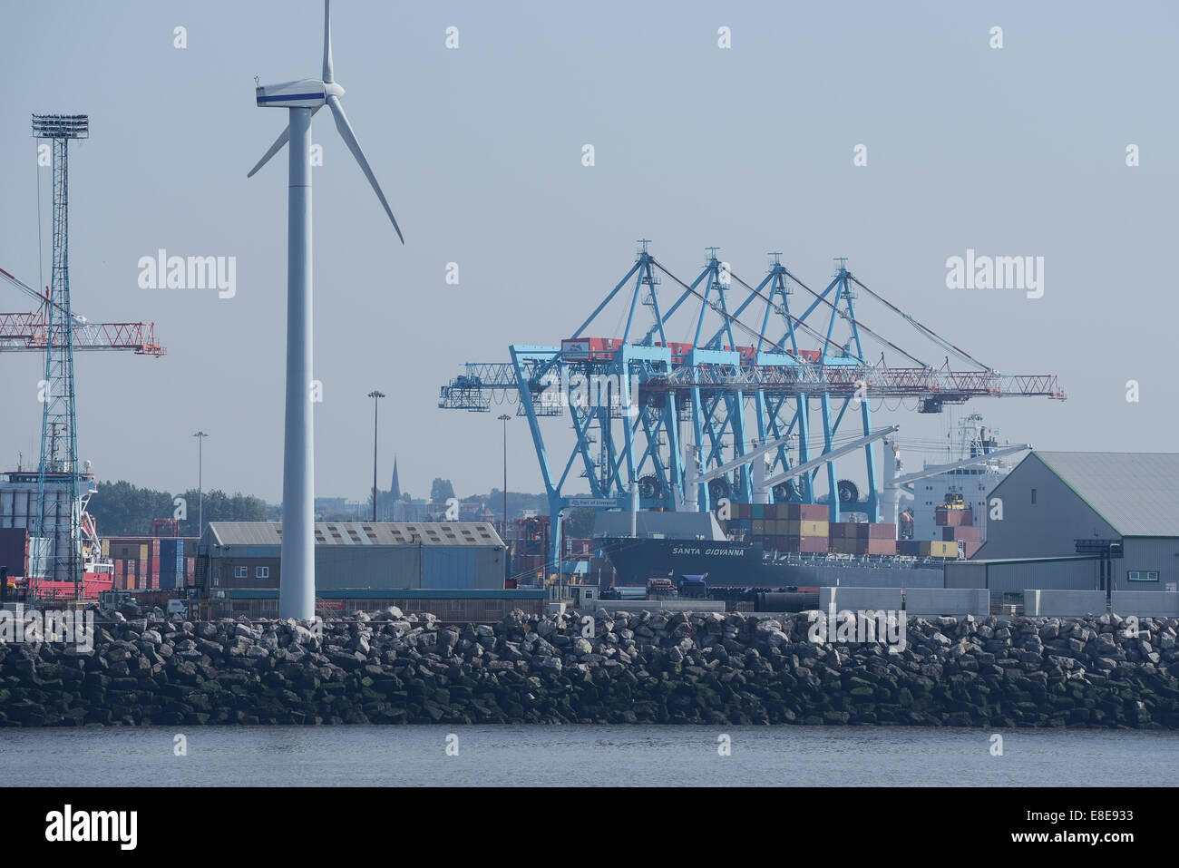 Gantry cranes working over a container ship at Liverpool docks UK - Stock Image