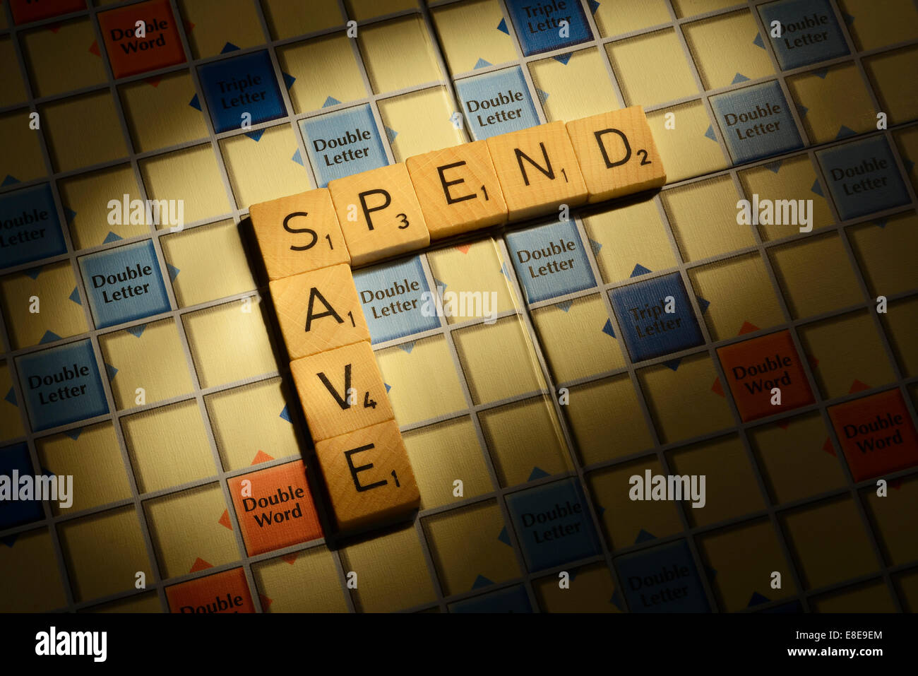 Scrabble board with the words Spend Save - Stock Image