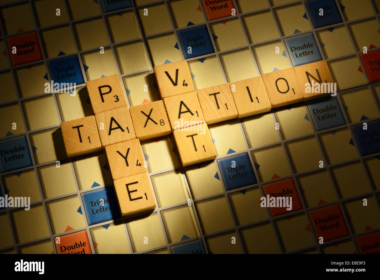 Scrabble board with the words Taxation PAYE VAT - Stock Image