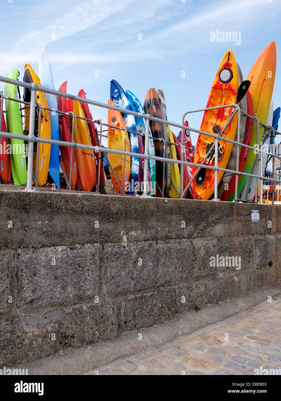 Colourful sit-on Kayaks for hire, Lyme Regis, Dorset, UK - Stock Image
