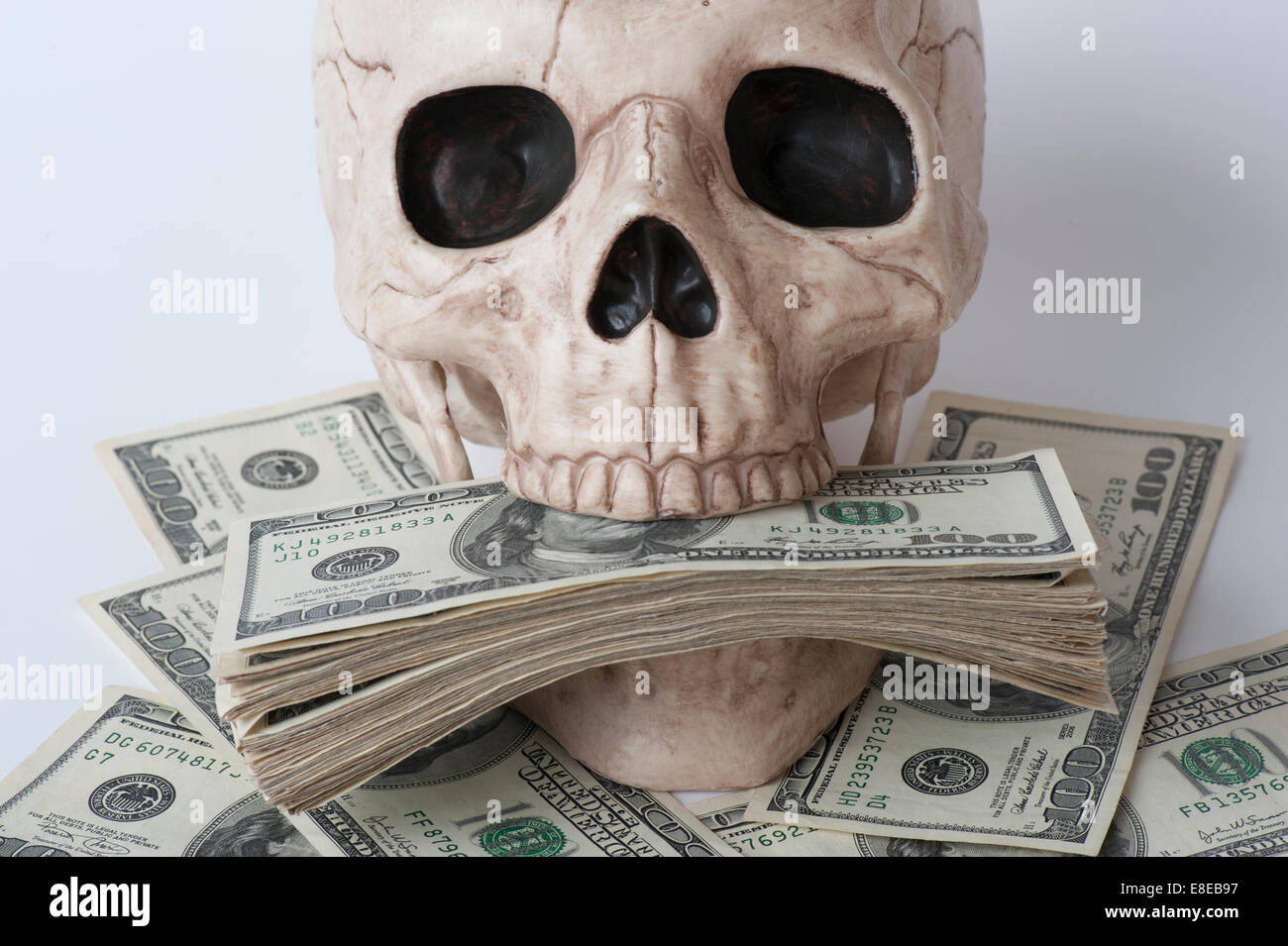 Human skull surrounded by stacks of one hundred dollar bills concept greed - Stock Image