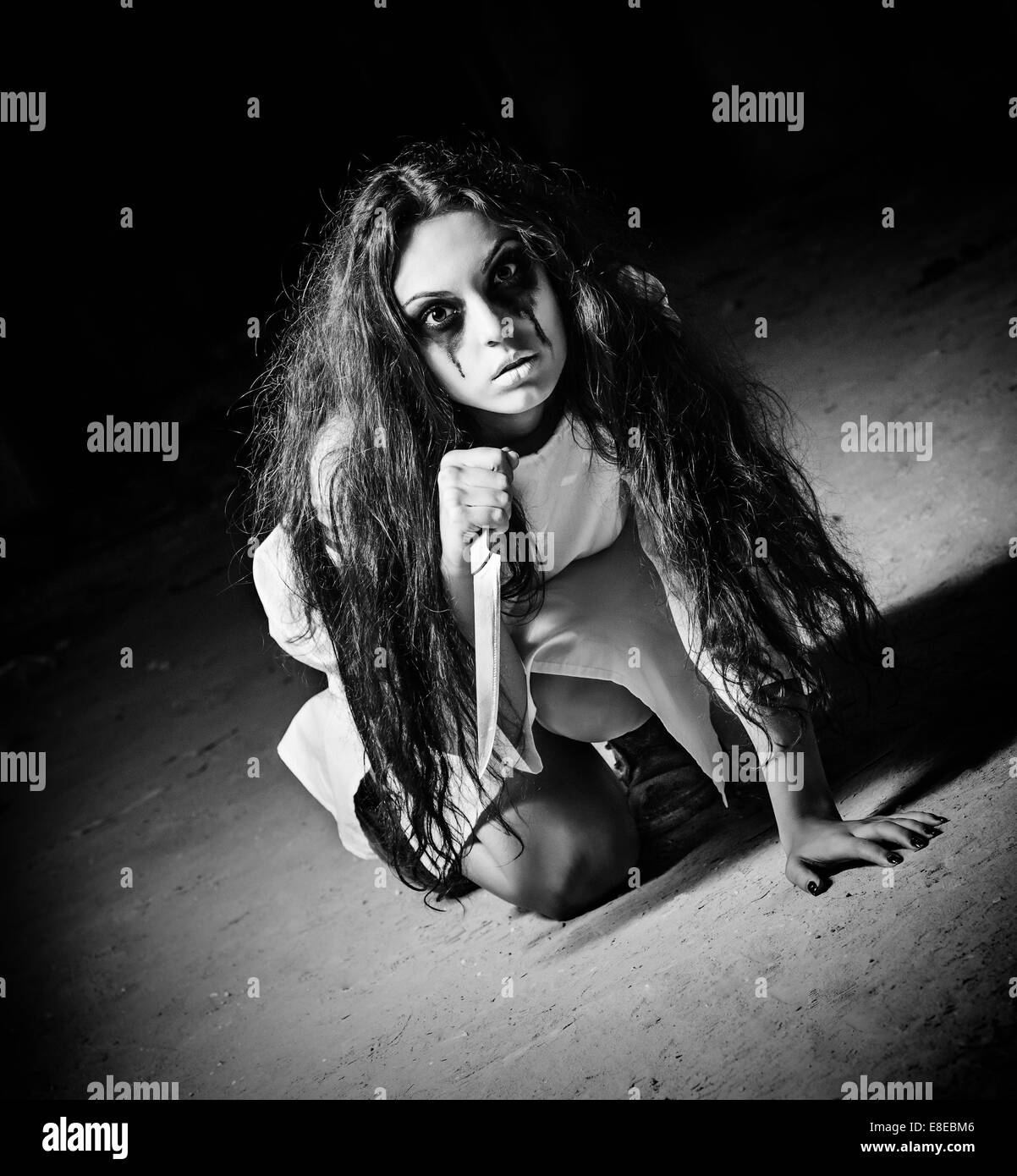 Horror shot a scary monster girl with knife in hands black and white
