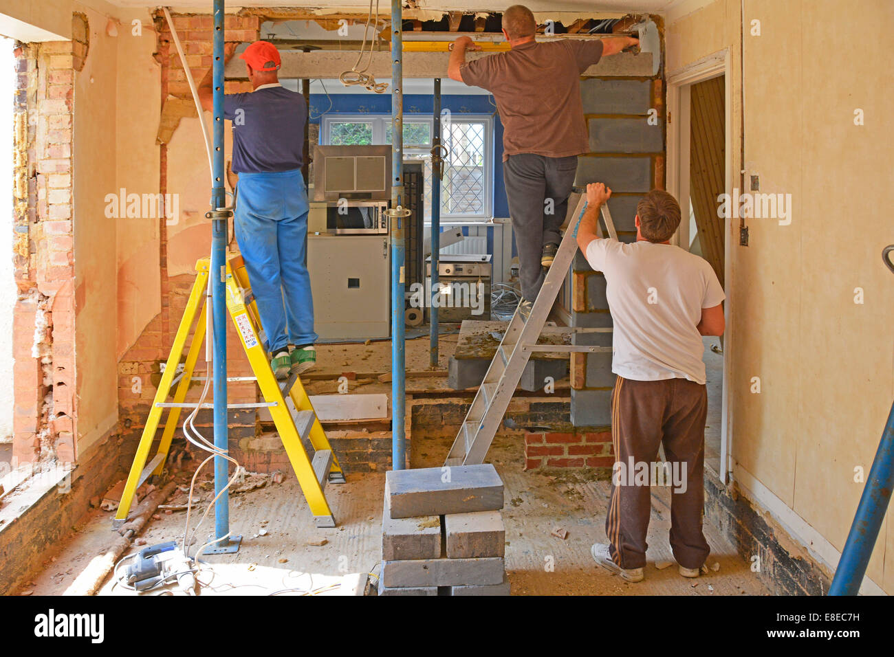 Builders at work install new lintel beam during major extension & alterations to detached house Brentwood Essex - Stock Image
