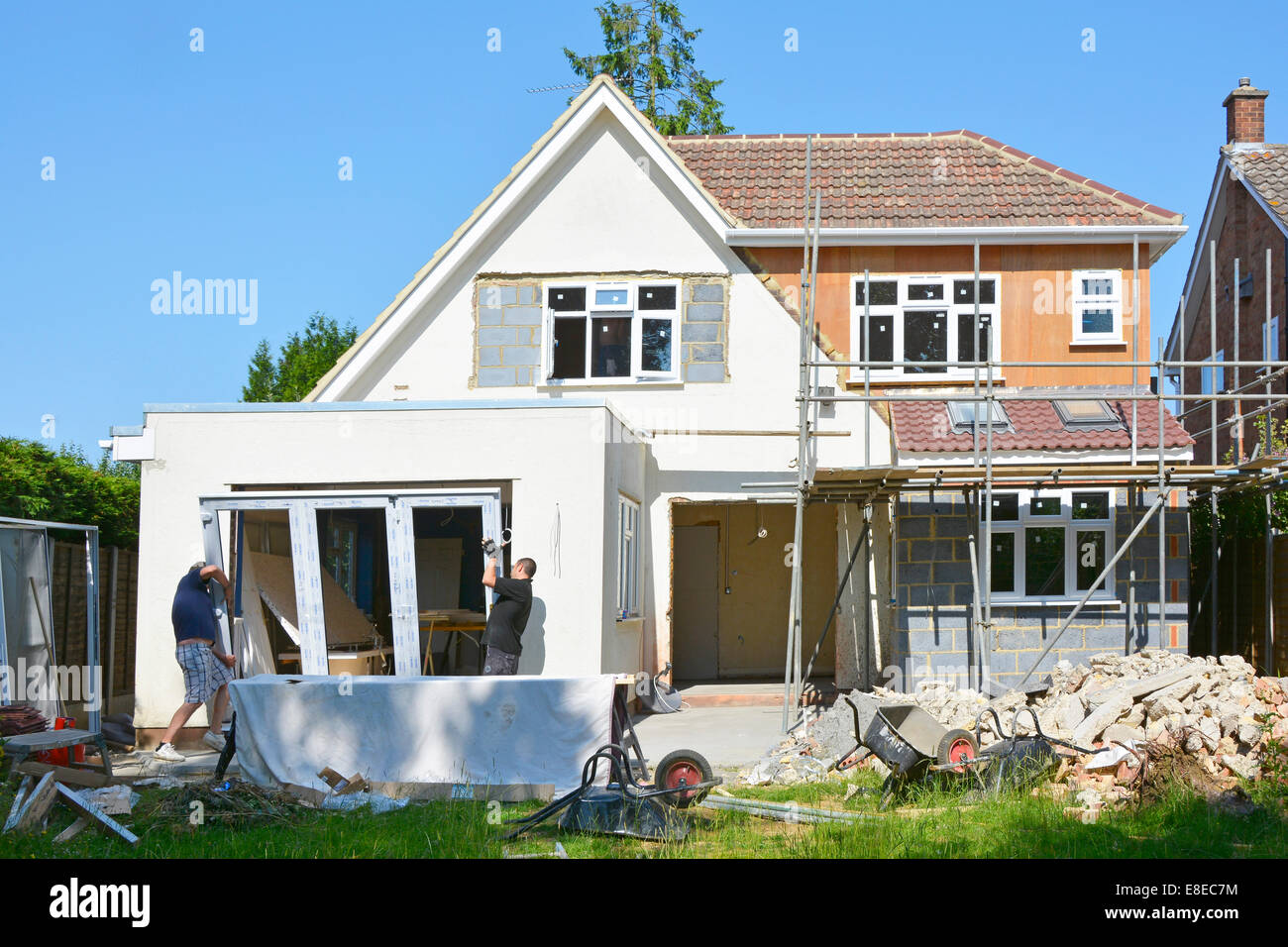 Workmen install UPVC fold back doors part of major extension to detached house Essex England UK (scaffold being - Stock Image