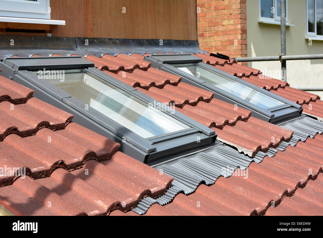 Roof lights & new tiles on roof on part of new kitchen extension to existing house shows lead & proprietary - Stock Image