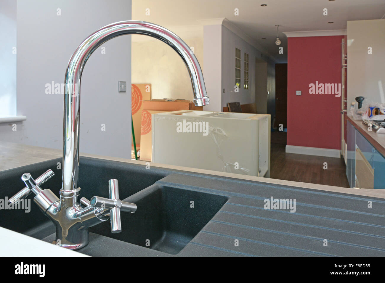 Kitchen sink and mixer tap close up during installation in new extension to detached house Essex England UK see - Stock Image