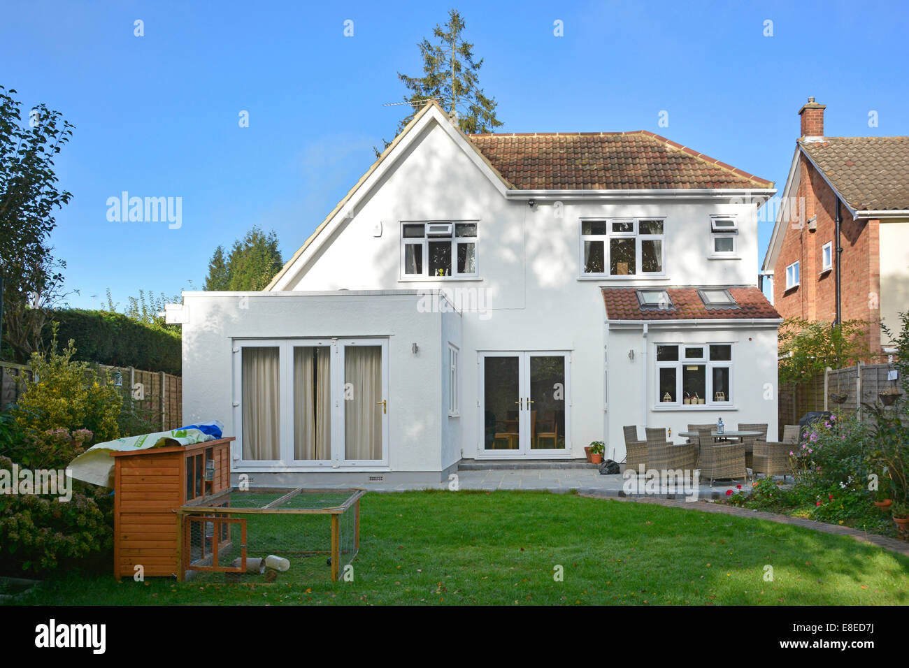 Completed two storey detached house side extension roof works & patio from back garden Essex England UK see - Stock Image