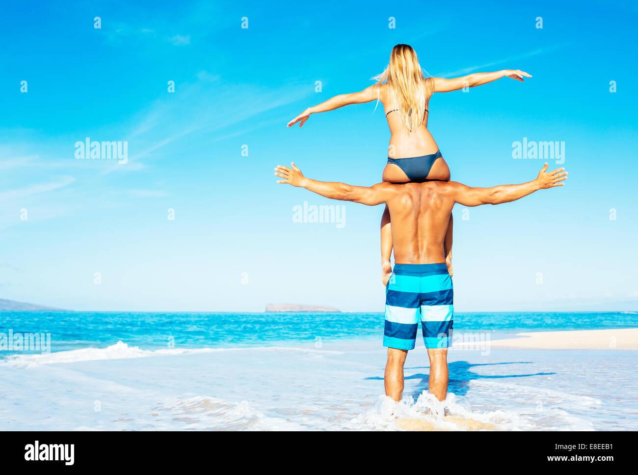 Happy Good Looking Couple Having Fun on Beautiful Sunny Beach - Stock Image