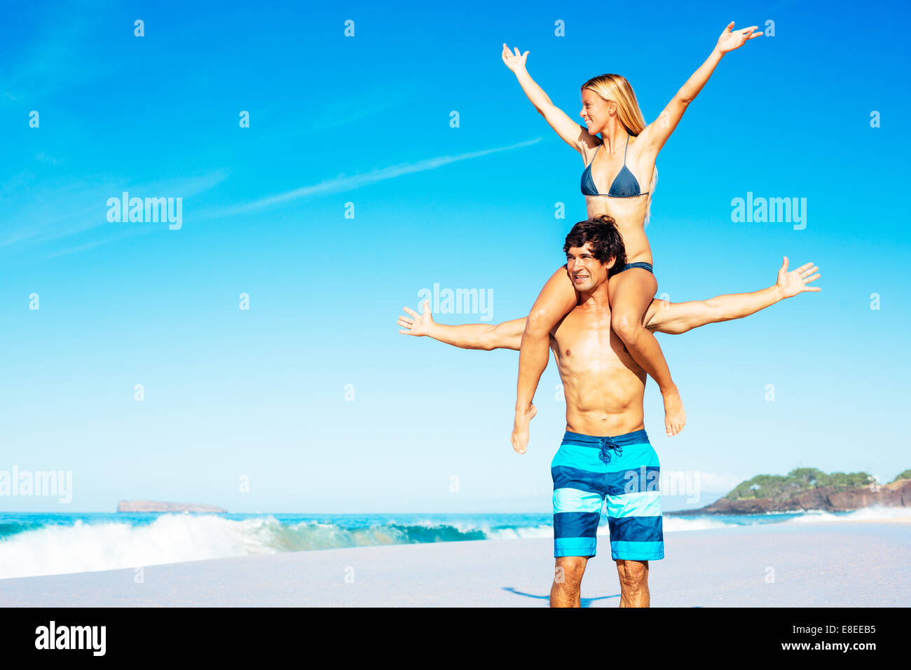 Happy Attractive Couple Playing and Having Fun on Beautiful Sunny Beach - Stock Image