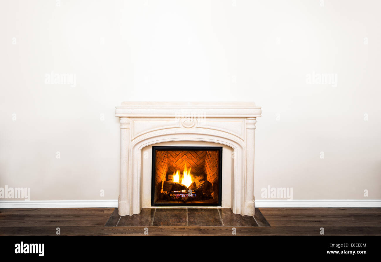 Luxurious White Marble Fireplace and empty wall for your text, logo, images, etc - Stock Image