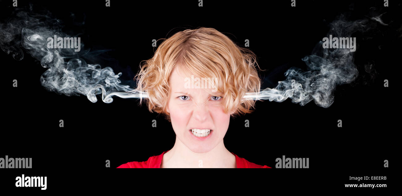 Very angry woman with smoke isolated on black background - Stock Image