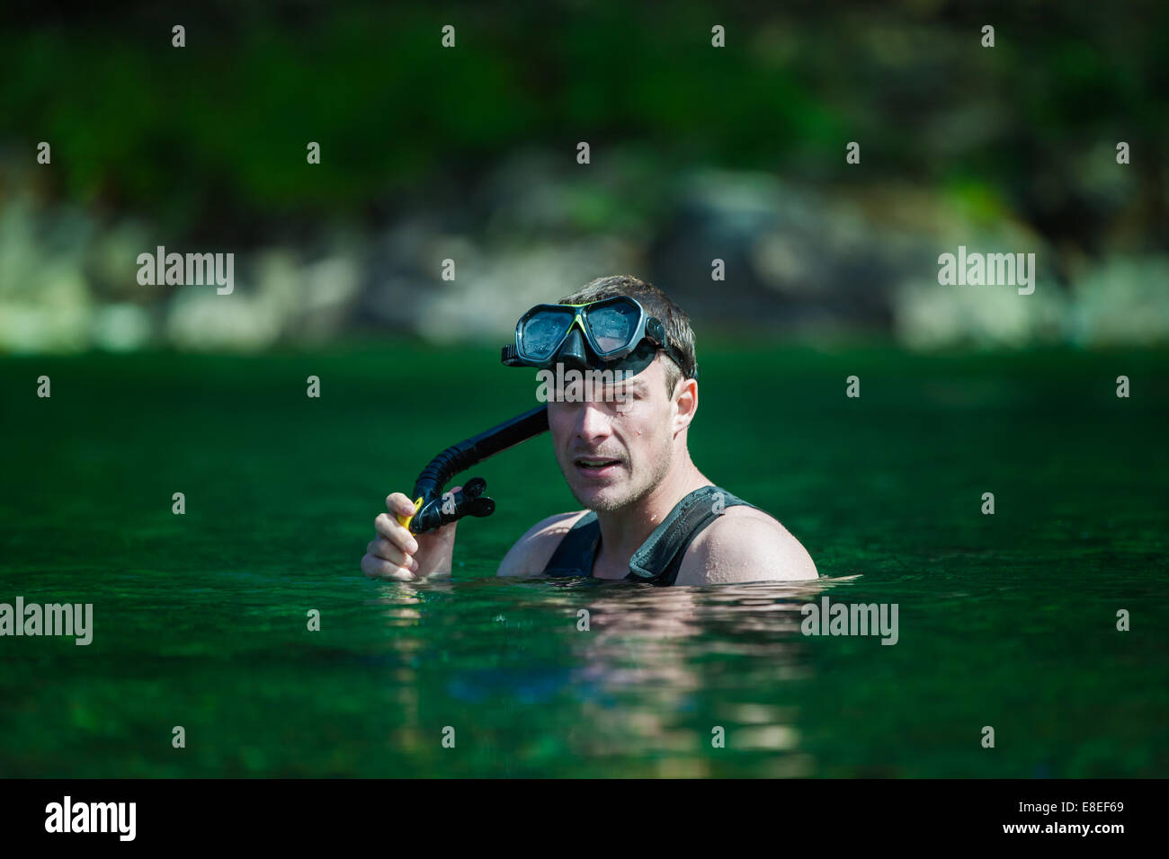 Young Adult Snorkeling in a river with Goggles and Scuba. - Stock Image