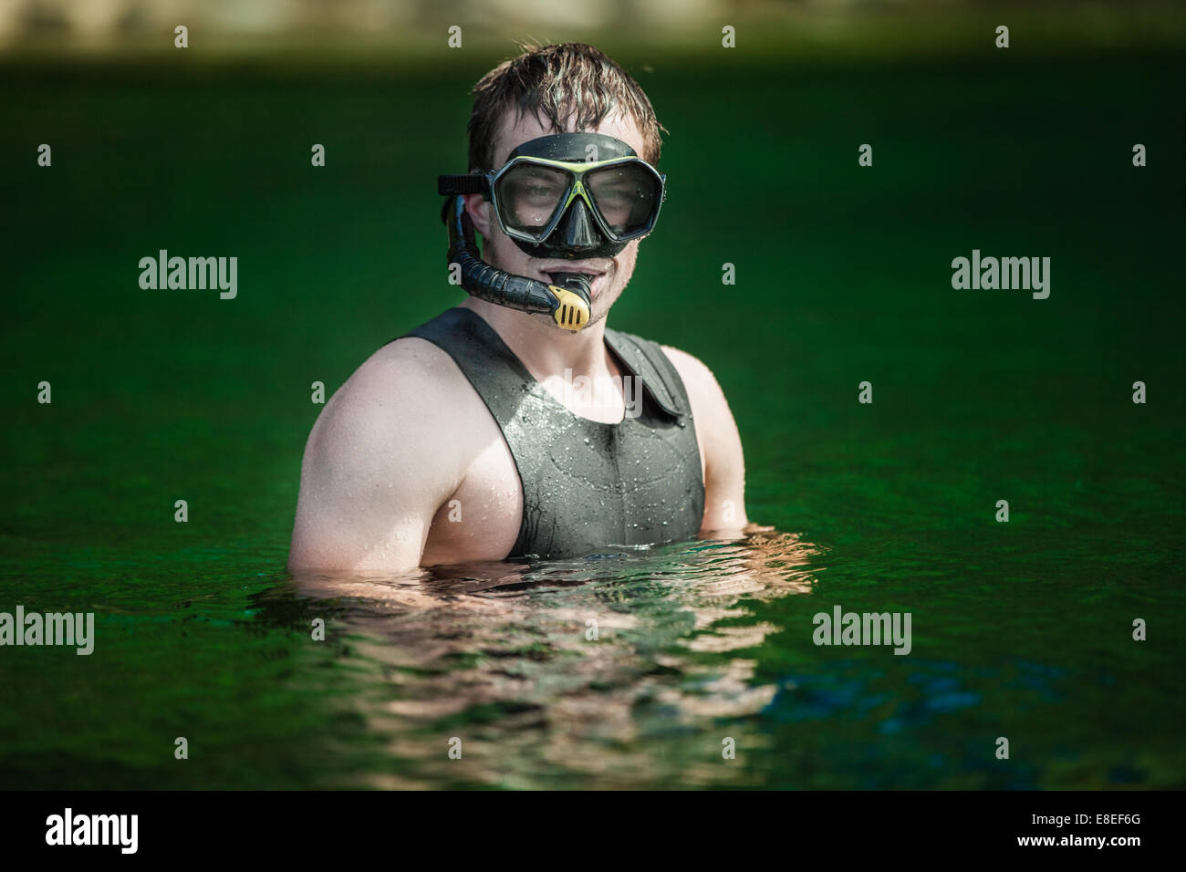 Funny Young Adult Snorkeling in a river with Goggles and Scuba. - Stock Image