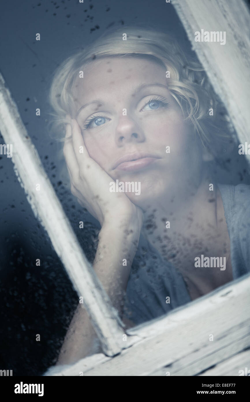 Bored Woman Looking at the Rainy Weather By the Window Frame - Stock Image