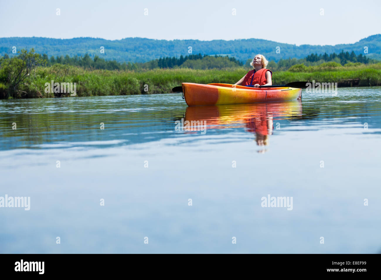 Young Woman Relaxing on a Kayak and Enjoying the Moment of Freedom - Stock Image