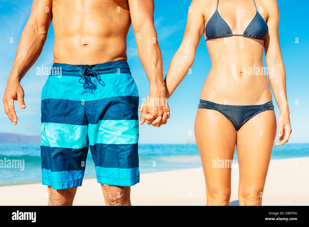 Attractive Fit Couple on the Beach in Swimwear Holding Hands - Stock Image