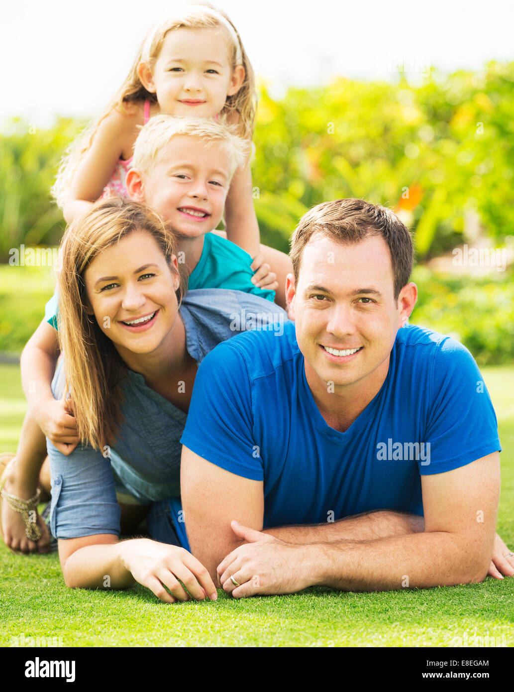 Portrait of Happy Family of Four Outside. Parents and Two Young Children - Stock Image