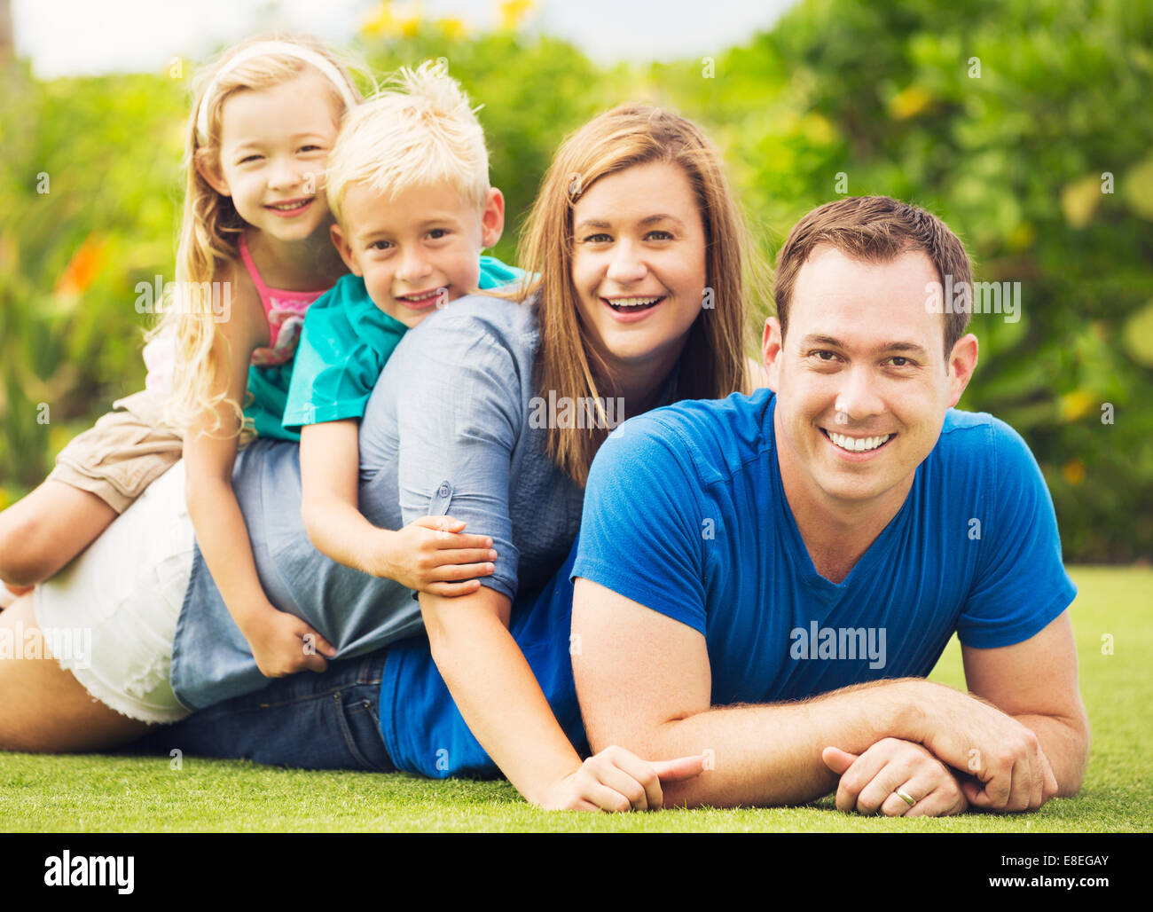 Portrait of Happy Family of Four Outside. Parents and Two Young Children Stock Photo