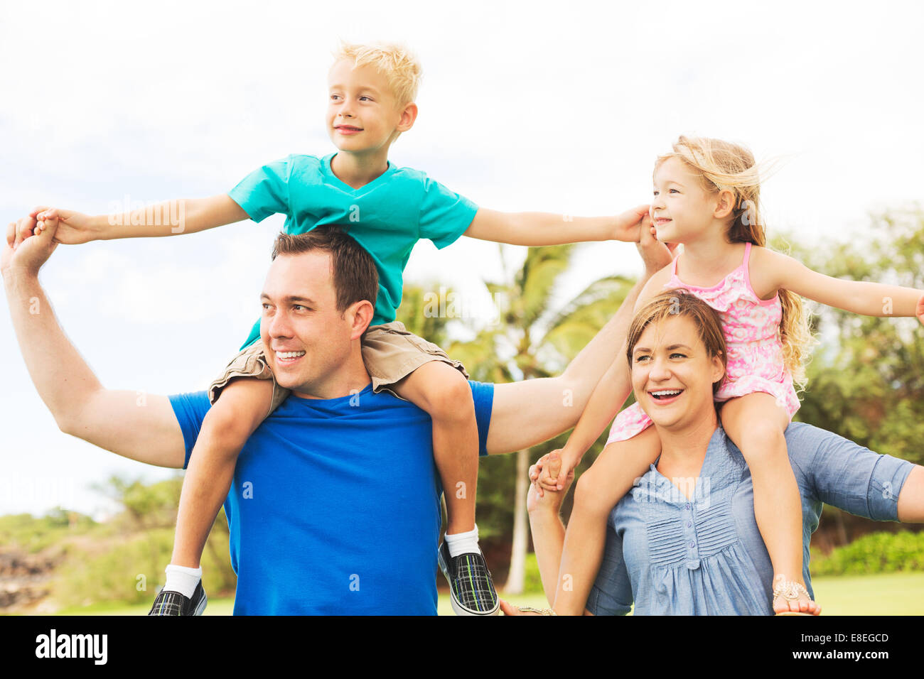 Portrait of Happy Family of Four Outside Playing - Stock Image