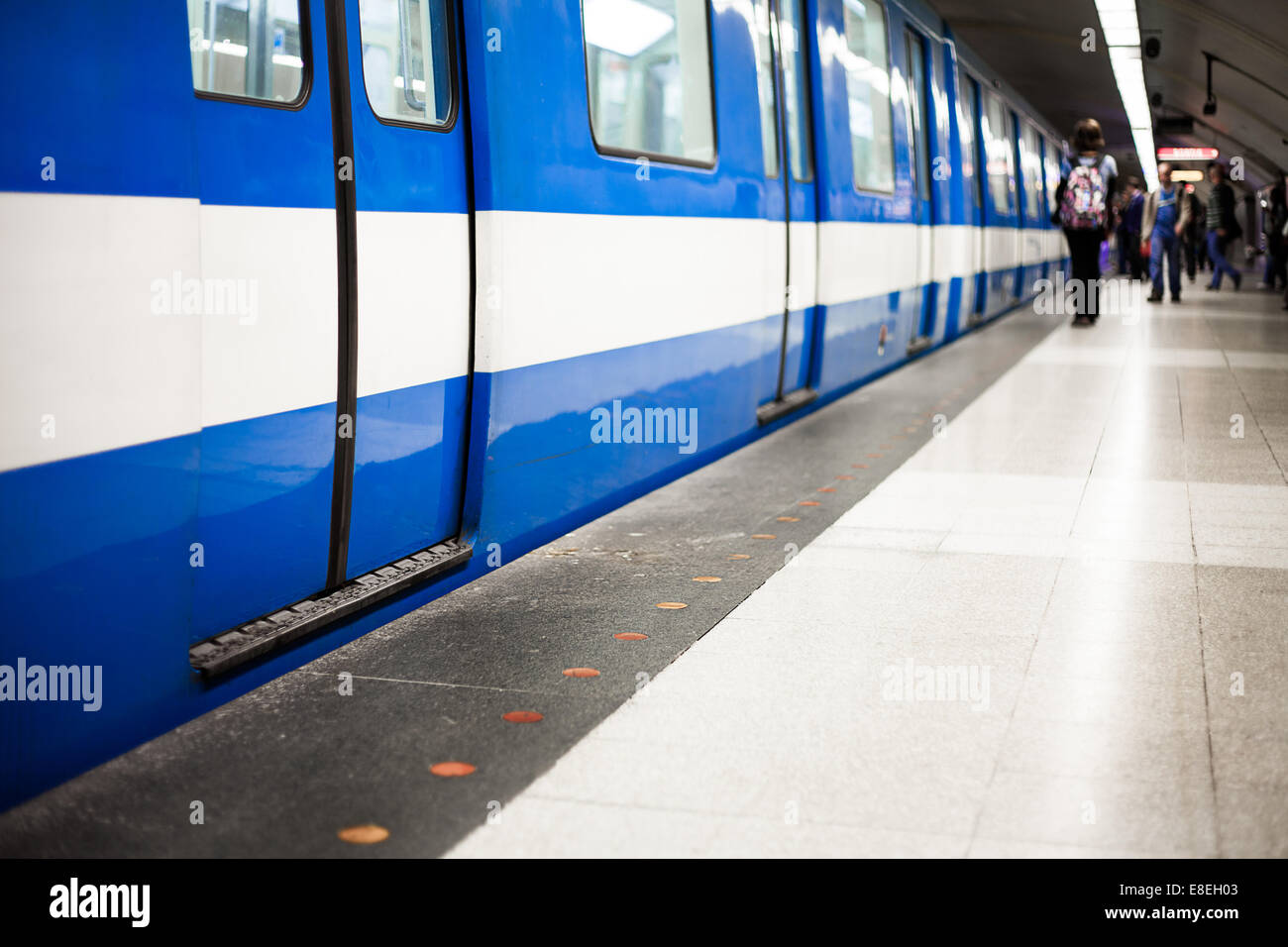 Colorful Underground Subway Train with blurry People on the Platform. Focus is on the door. room for your text. Stock Photo