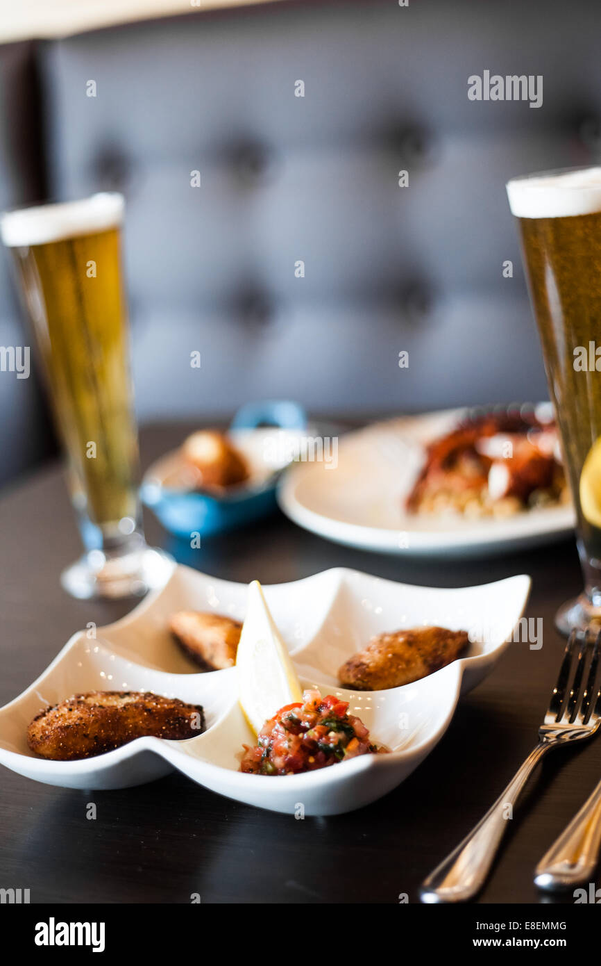 Traditional Portuguese Food and Blonde Draft Beer on a Table in a Restaurant - Stock Image