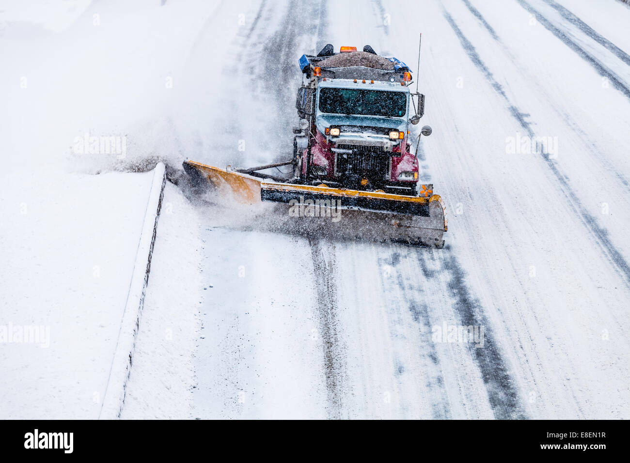 Snowplow Truck Removing the Snow from the Highway during a Cold Snowstorm Winter Day - Stock Image