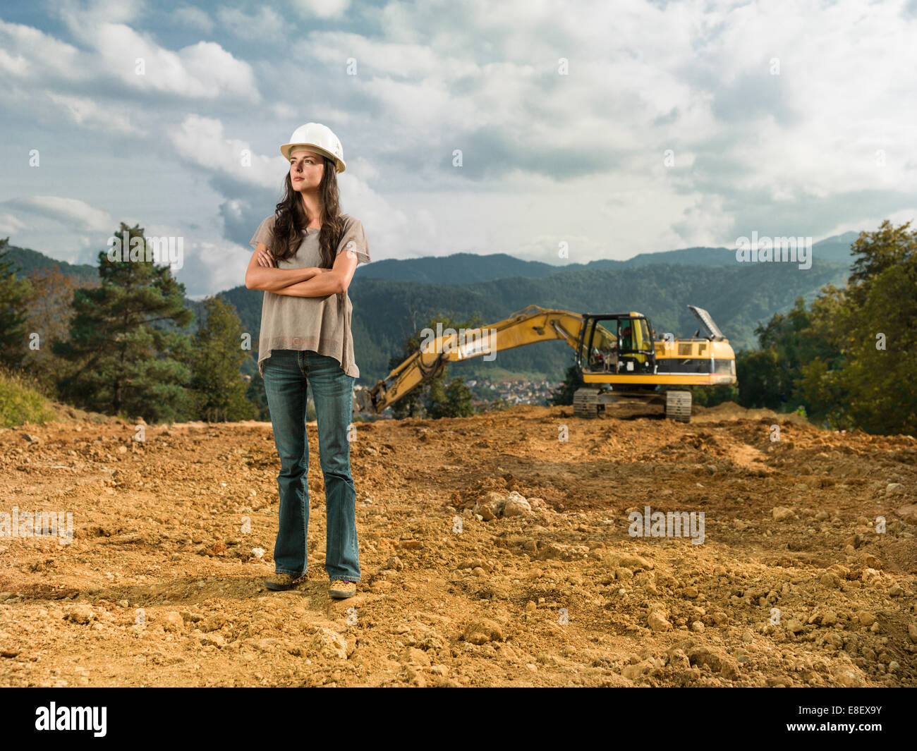 female engineer standing with her arms crossed on construction site outdoors - Stock Image