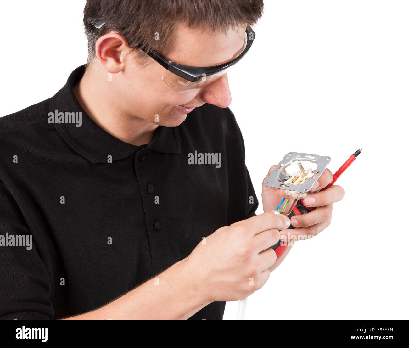 Male serviceman working with cables and electrical outlet. - Stock Image