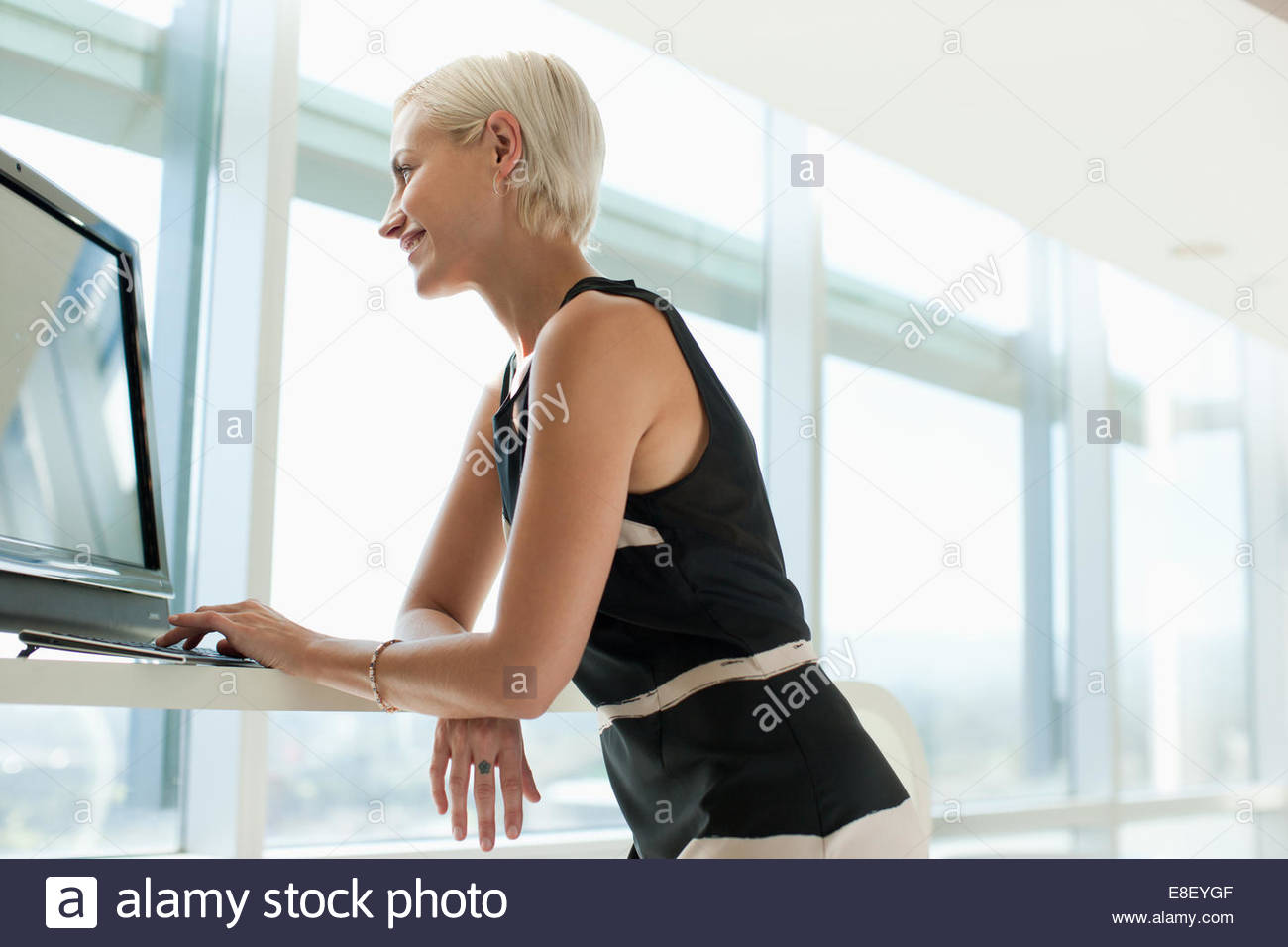 Businesswoman using computer in office - Stock Image