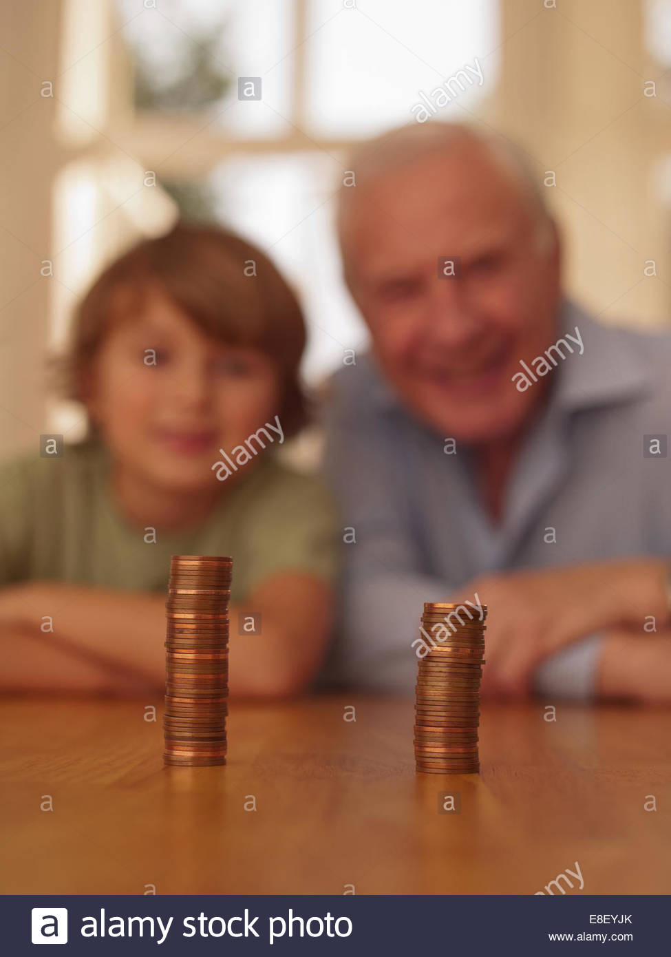 Grandfather and grandson looking coins - Stock Image