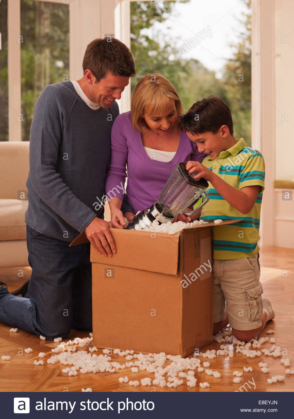 Family opening box in living room - Stock Image