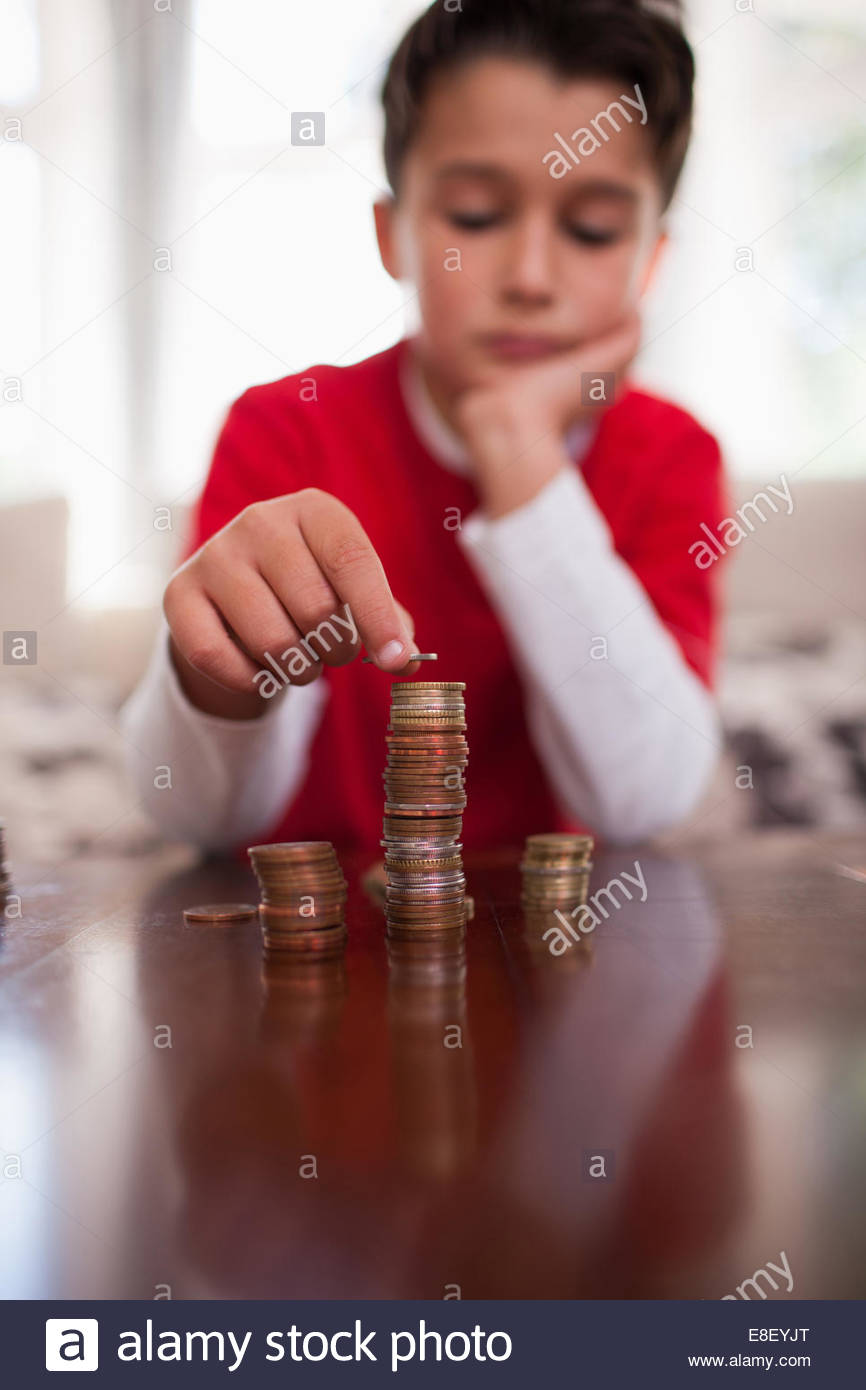 Smiling boy stacking coins - Stock Image