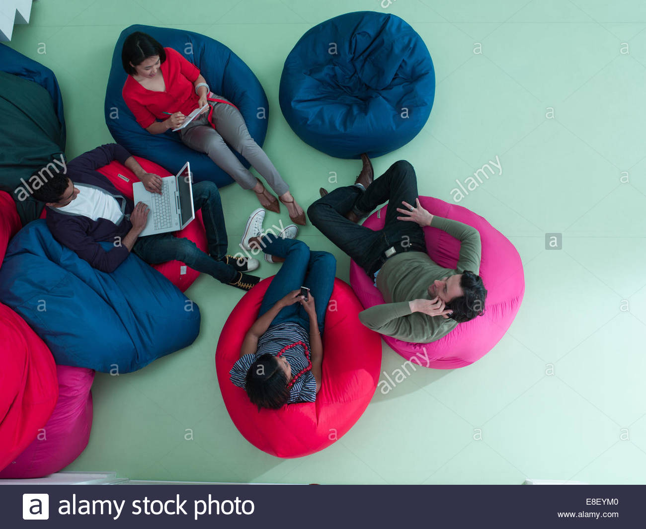 Men and women using laptop and cell phones in bean bag chairs - Stock Image
