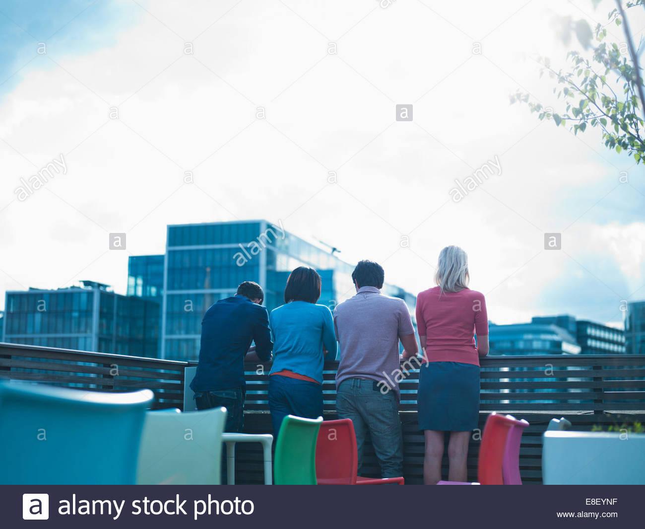 Smiling men and women talking on urban balcony - Stock Image