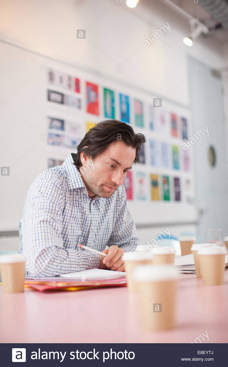 Businessman working with surrounded by coffee cups in office - Stock Image