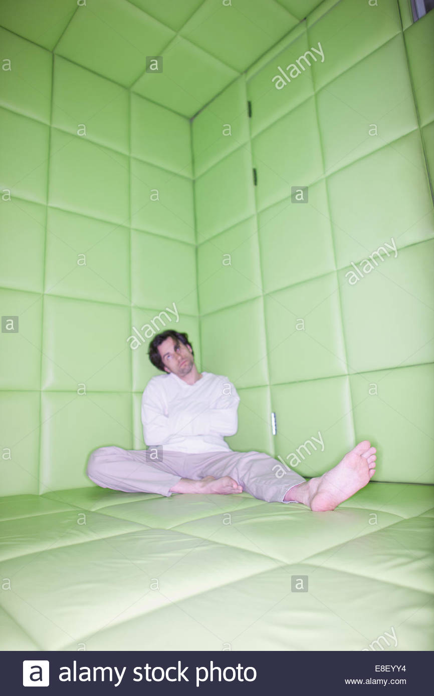 Man sitting with legs apart in padded room - Stock Image