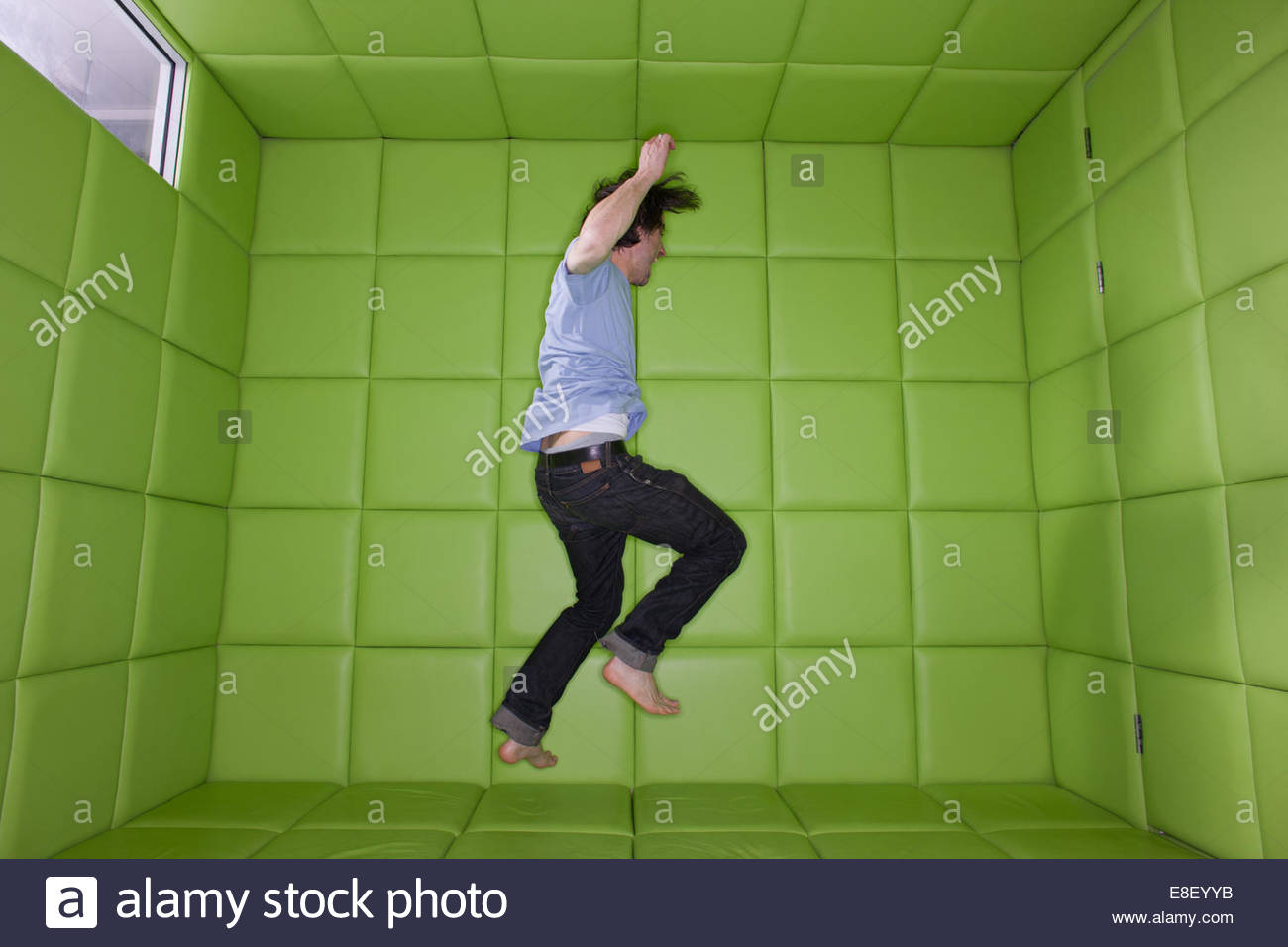 Man dancing in padded room - Stock Image