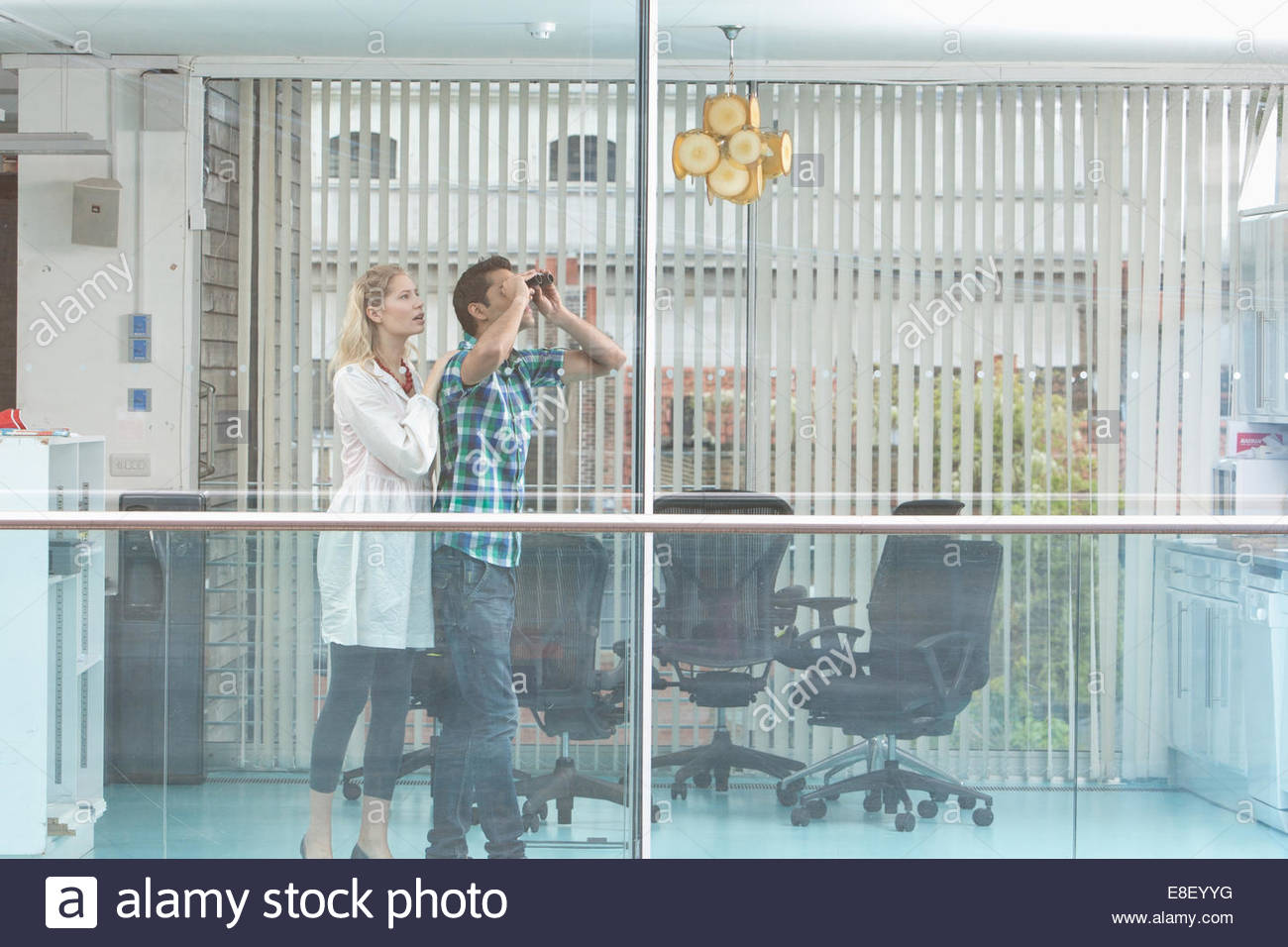Smiling man and woman looking out window - Stock Image