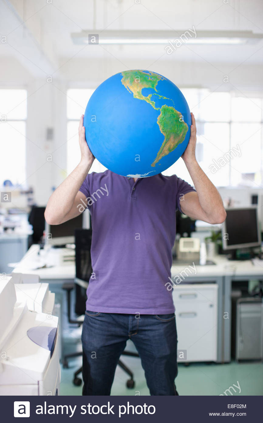 Businessman holding globe over face in office - Stock Image