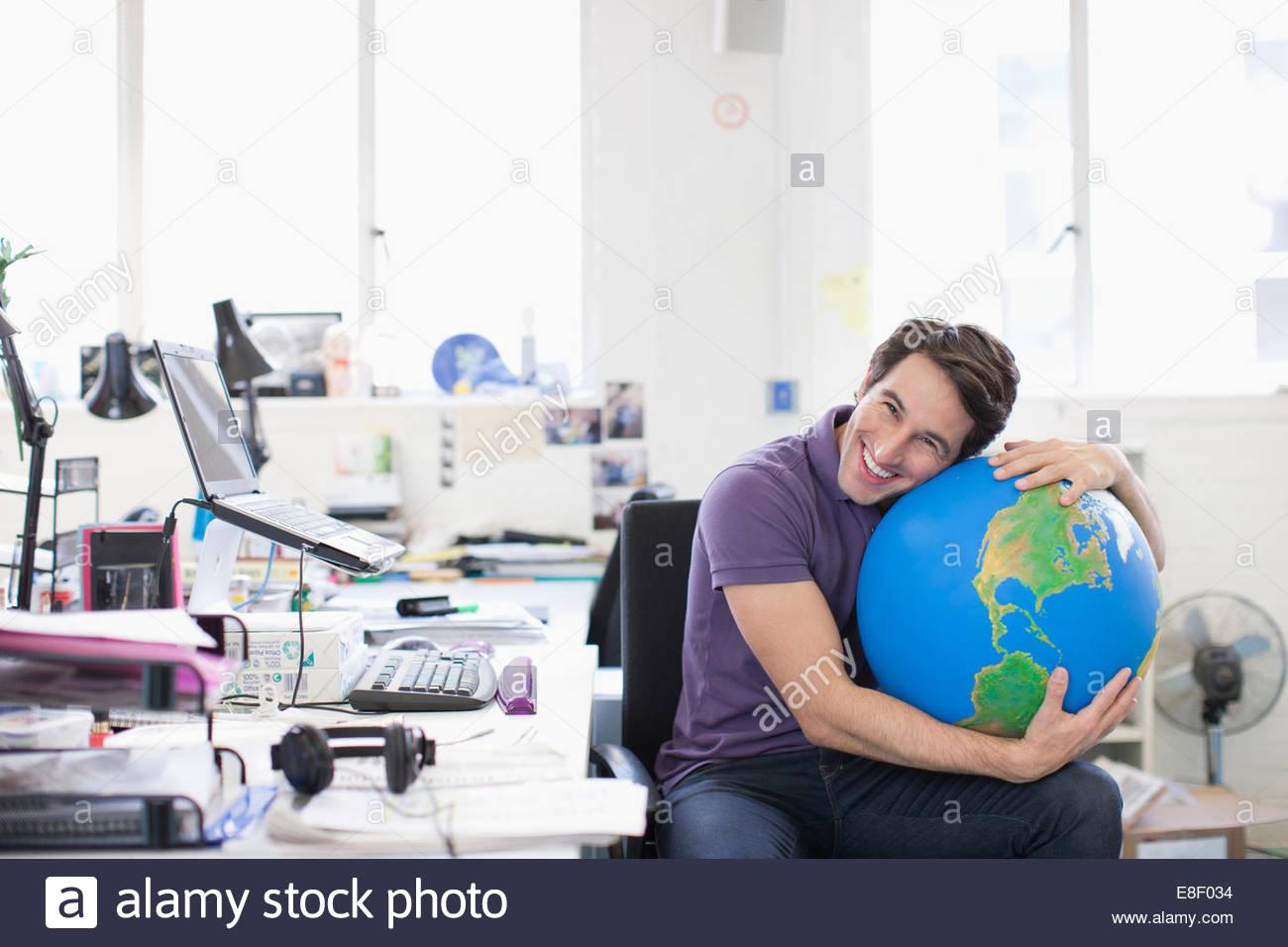 Smiling businessman hugging globe at desk in office - Stock Image