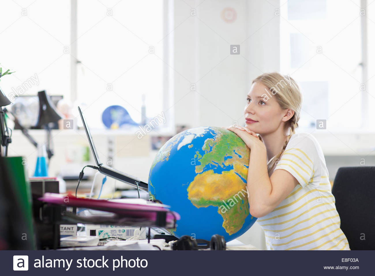 Pensive businesswoman leaning on globe at desk in office - Stock Image