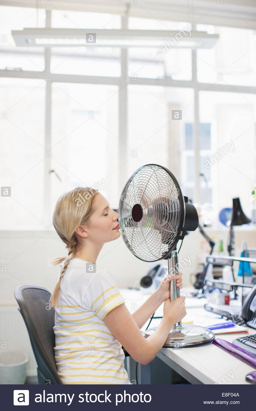 Smiling woman sitting in front of fan in office - Stock Image