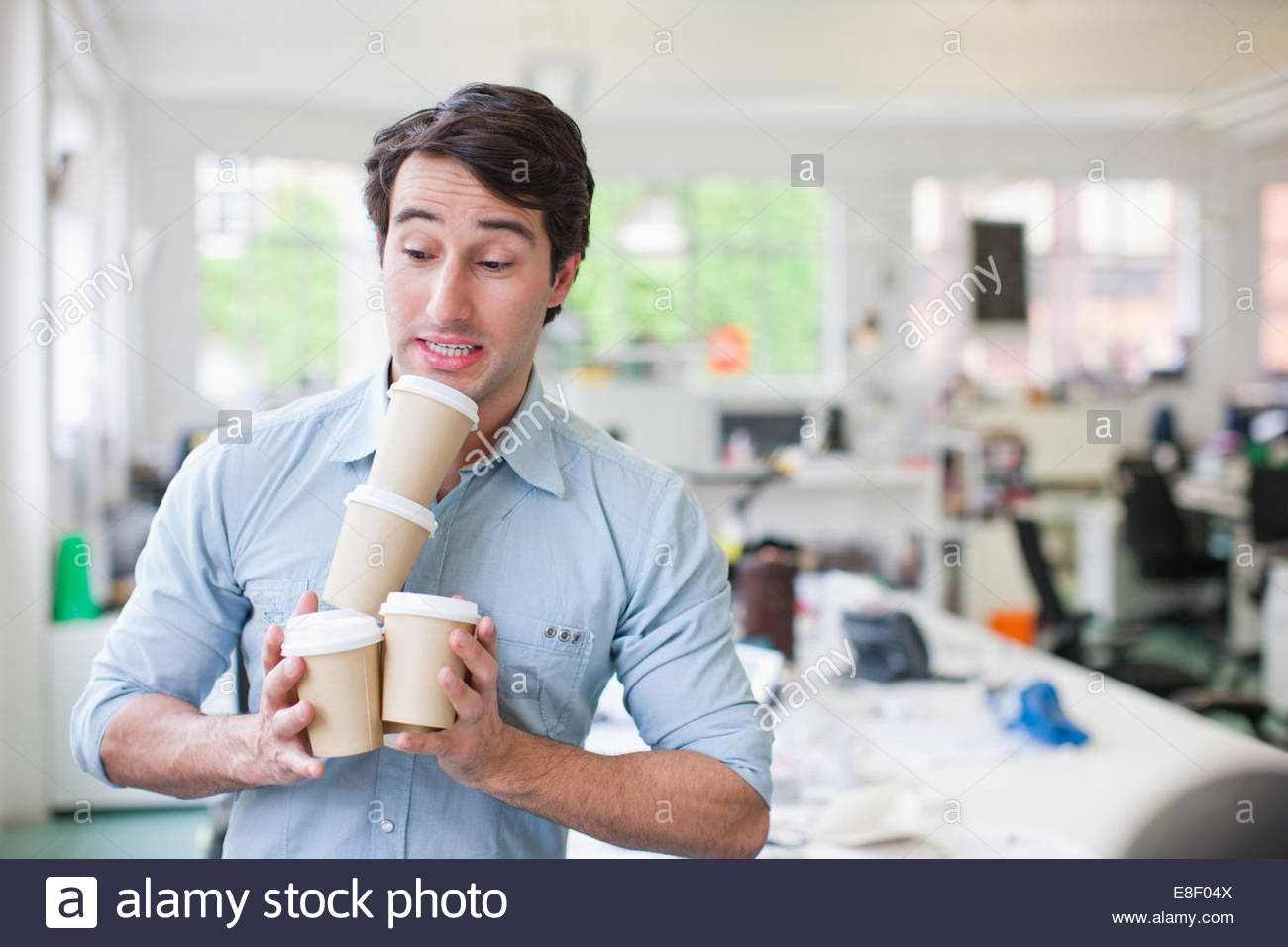 Businessman balancing coffee cups - Stock Image