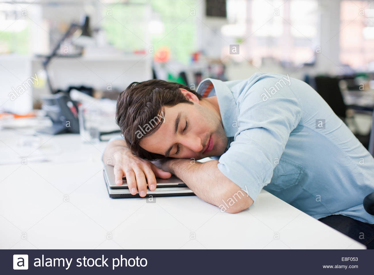 Businessman sleeping on laptop at desk in office - Stock Image