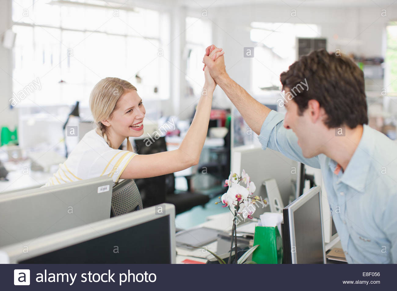 Business people holding hand in office - Stock Image