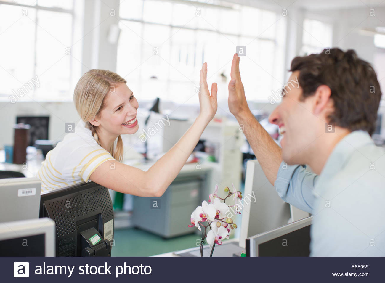 Business people giving high five in office - Stock Image